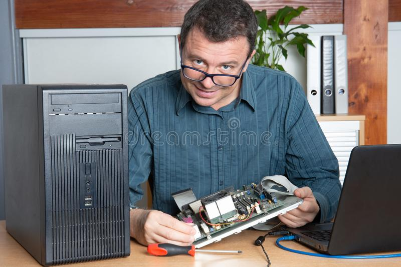 Technician repair computer man in support service office. A technician repair computer man in support service office royalty free stock image