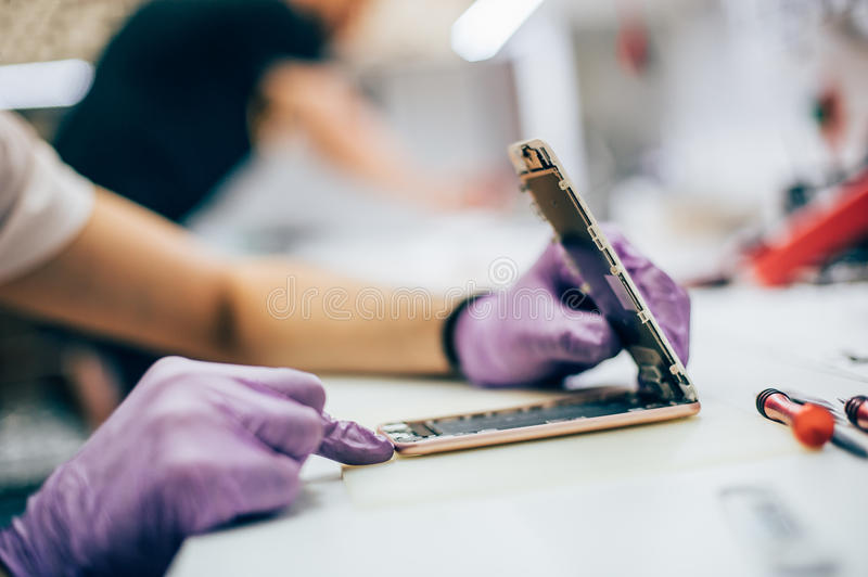 Technician repair faulty mobile phone in electronic smartphone t. Echnology service. Cellphone technology device maintenance engineer royalty free stock photos