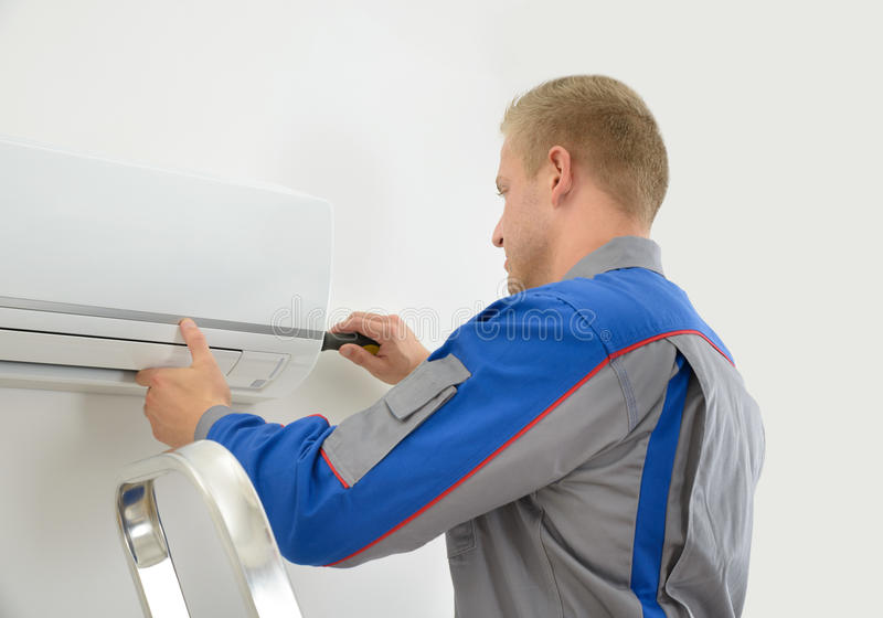 Technician Repairing Air Conditioner. Portrait Of Young Male Technician Repairing Air Conditioner royalty free stock photo