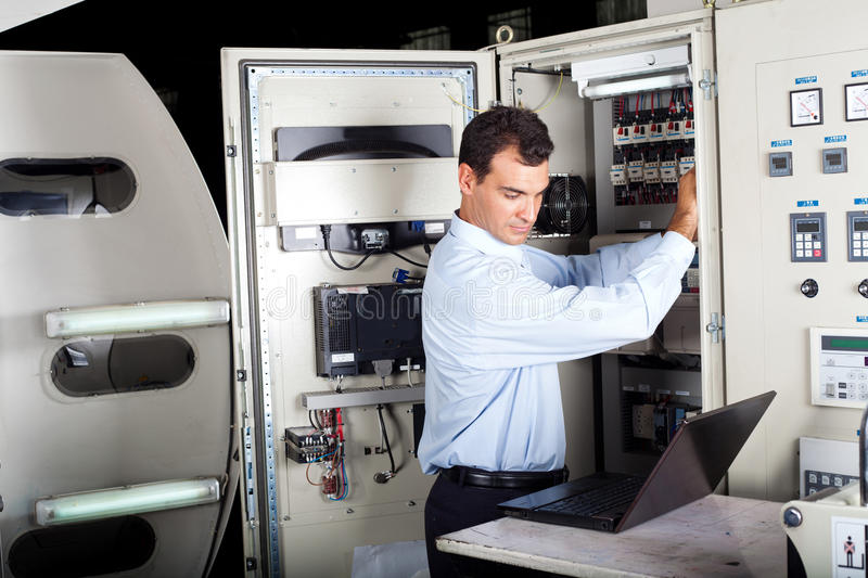 Technician repairing computerized machine. Industrial technician repairing modern computerized machine in factory royalty free stock images