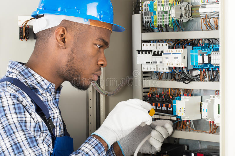 Technician Repairing Fusebox With Screwdriver stock photo