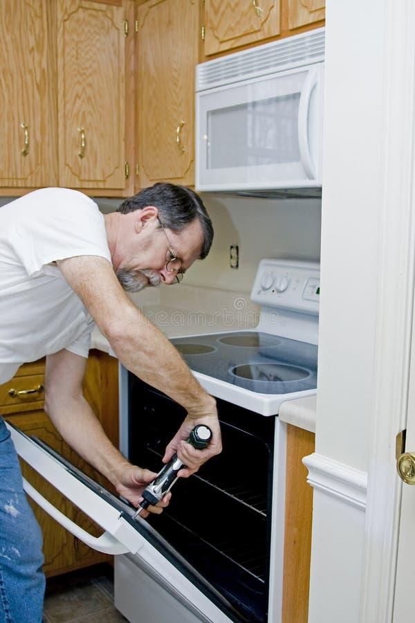 Technician repairing oven door stock photos