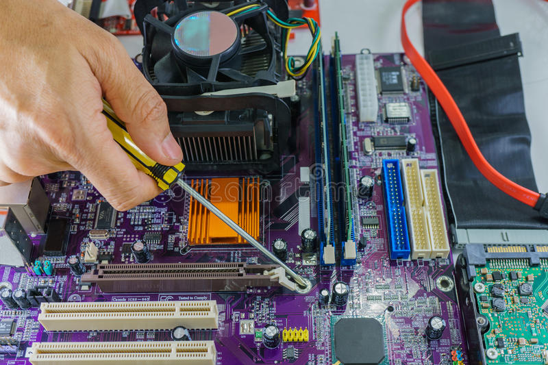 Technician's hands fixing mainboard with screwdriver royalty free stock photo