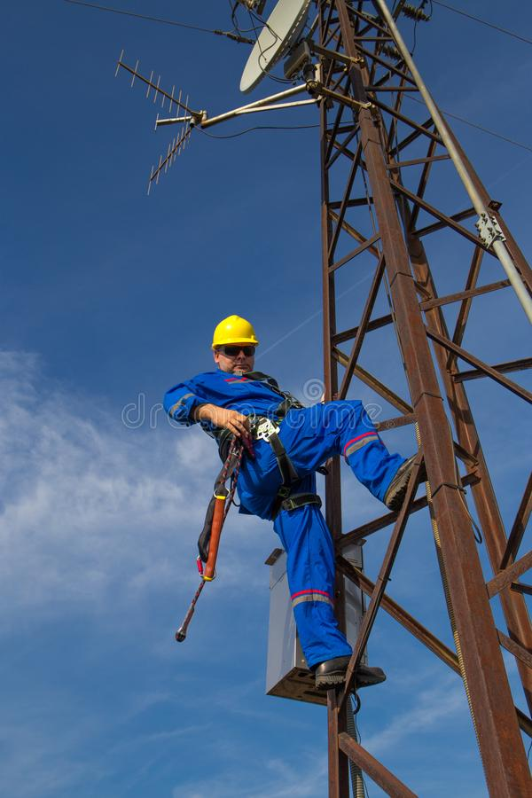 Technician with safety belt working on electric power pole stock photos