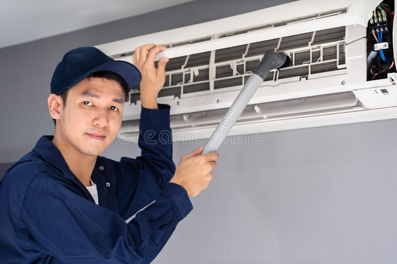 Technician service using vacuum cleaner to cleaning air conditioner. Technician service using vacuum cleaner to cleaning the air conditioner royalty free stock photos