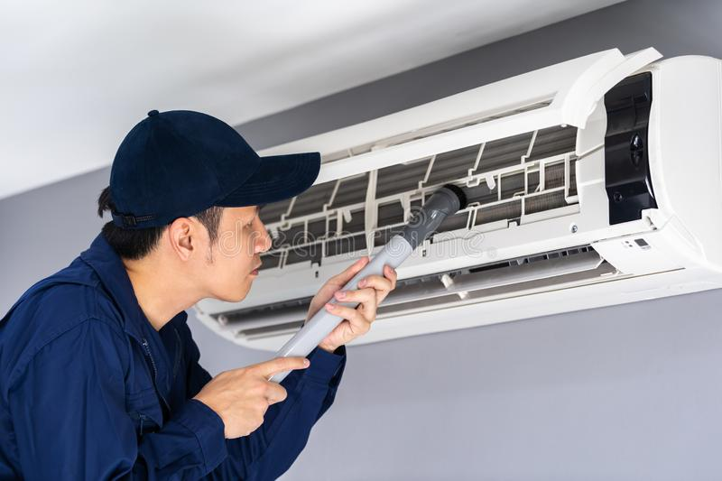 Technician service using vacuum cleaner to cleaning air conditioner. Technician service using vacuum cleaner to cleaning the air conditioner stock image