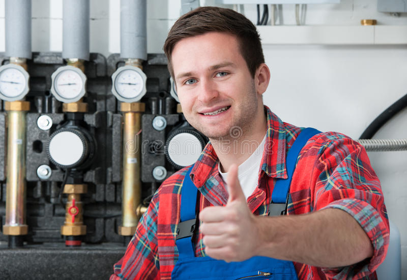 Technician servicing heating boiler. Technician servicing the gas boiler for hot water and heating stock images
