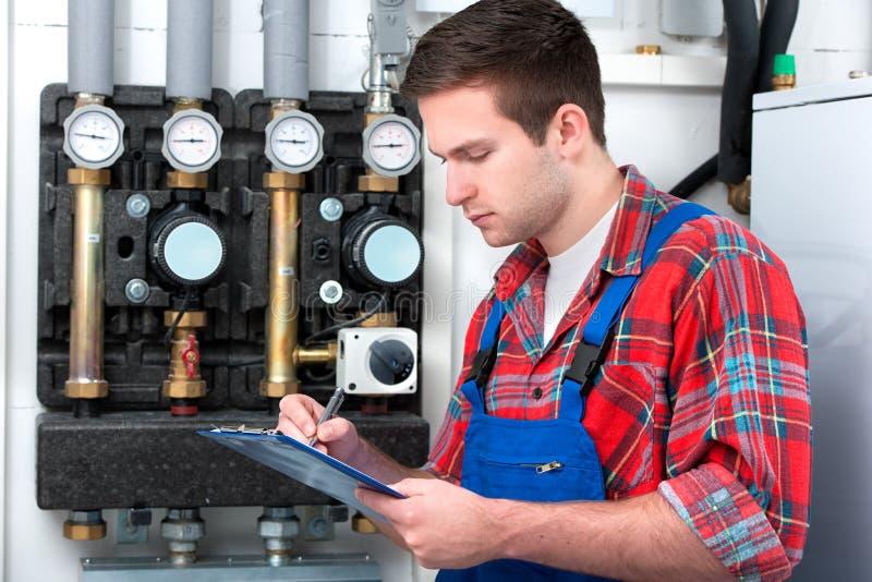 Technician servicing heating boiler royalty free stock photos