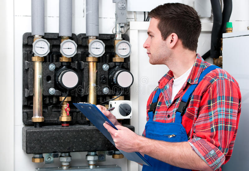 Technician servicing heating boiler royalty free stock photo