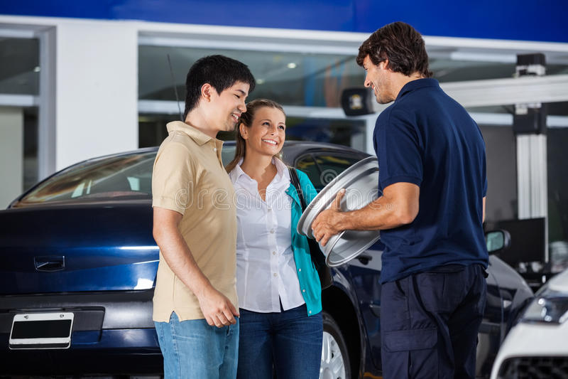 Technician Showing Metallic Hubcap To Couple. Happy male technician showing metallic hubcap to couple at garage stock photography