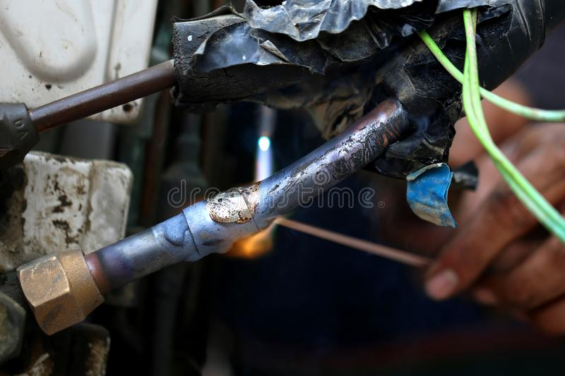 Technician are soldering a coil with copper in order to fix leakage of air compressor. This is a oil and piping problem of air-con. Ditioner royalty free stock photo