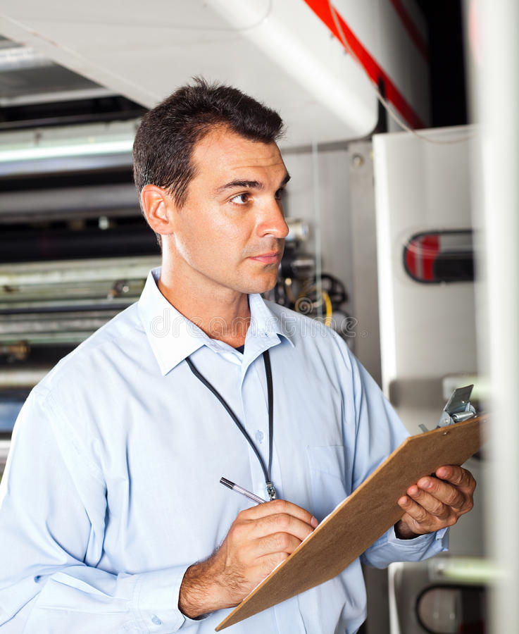 Technician taking machine readings. Industrial technician taking machine readings royalty free stock photography