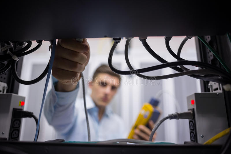 Technician using cable tester while fixing server. In large data center stock images