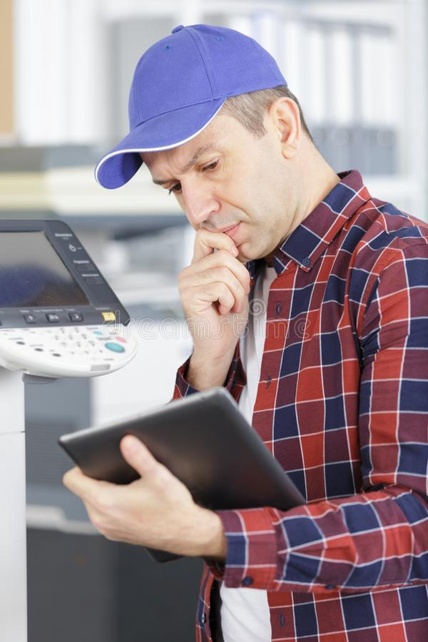 Technician using tablet to fix printer stock images