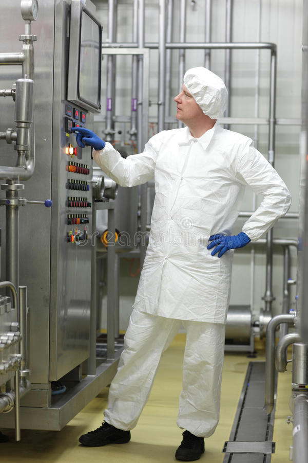 Technician in white coveralls and cap controlling industrial process in plant. Caucasian biotechnology technician in white coveralls and cap controlling stock image