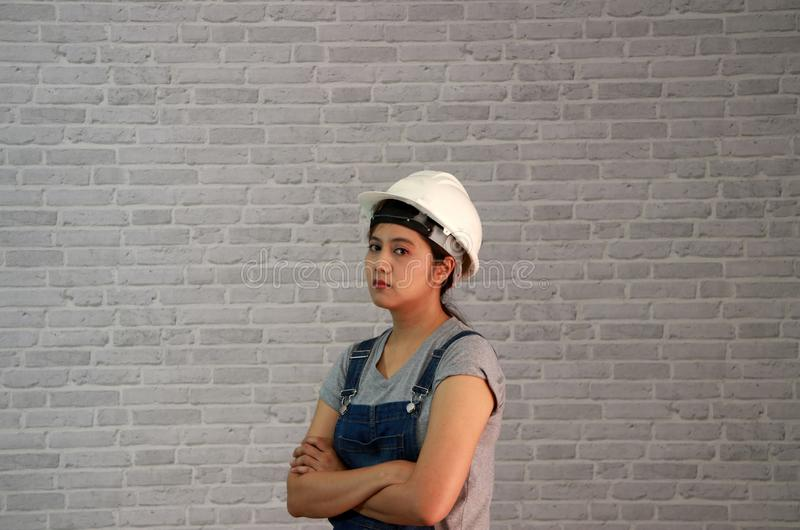 Technician woman ware white helmet with grey T-shirt and denim jeans apron dress standing forty five angle and hugging chest. royalty free stock photo