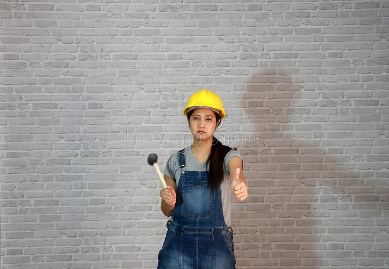 Technician woman ware yellow helmet with grey T-shirt and denim jeans apron dress standing with rubber hammer in hand and thumb up. Technician woman ware yellow stock photos