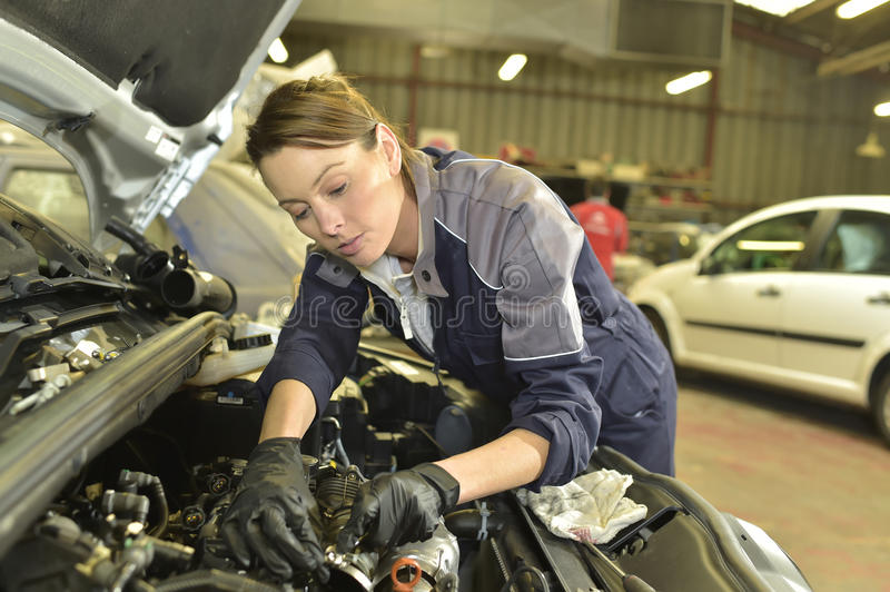 Technician woman working in car garage royalty free stock images