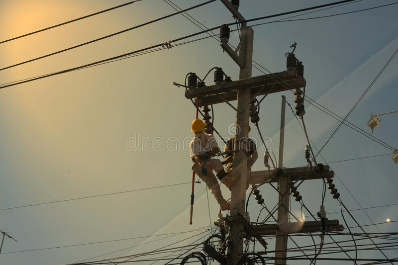 Technician work on high voltage electicity pole with copy space and reflect light stock image