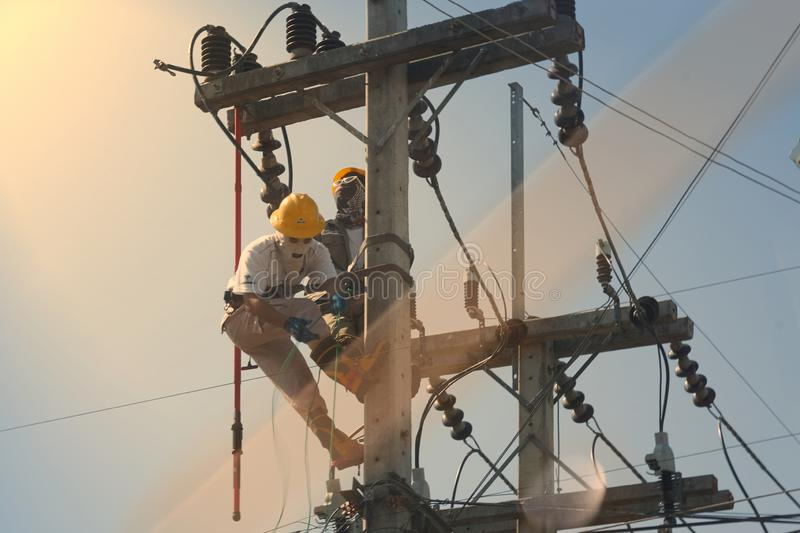 Technician work on high voltage electicity pole and reflect light stock photography