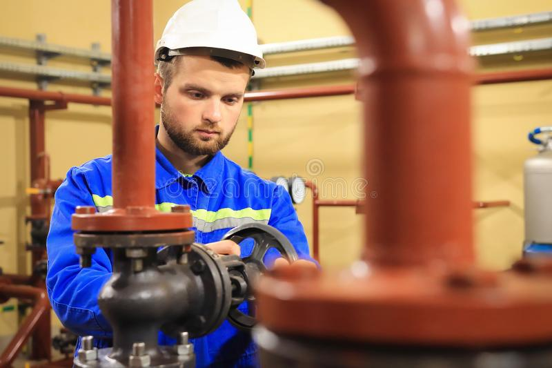 Technician worker on heating system. Station operator opens water valve on pipeline. Man works on industrial boiler stock photography