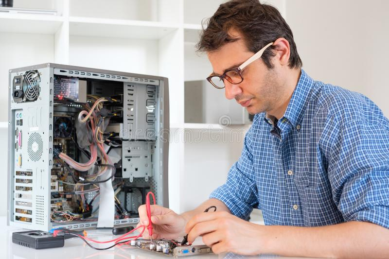 Technician working on broken computer in his office. Engineer disassembling a computer internal parts in service center royalty free stock photos