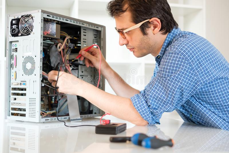 Engineer disassembling a computer internal parts in service center. Technician working on broken computer in his office stock image