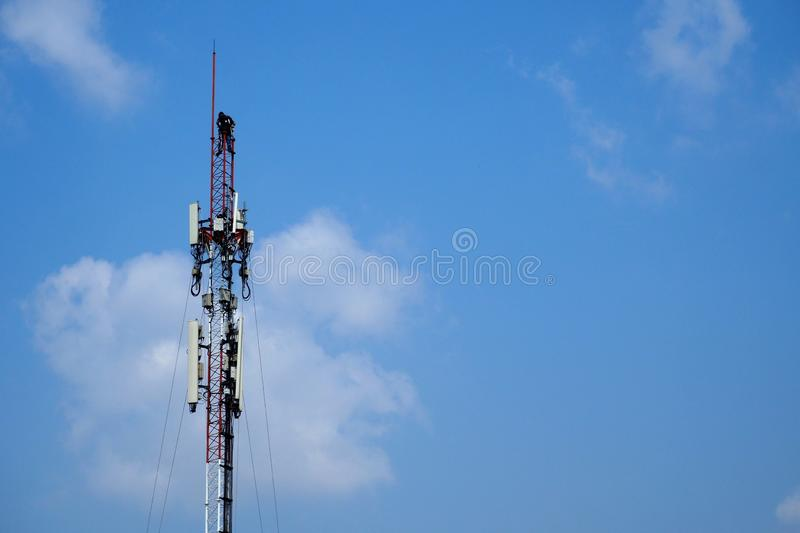 Technician working on cellular telecom pole. High tower with blue sky background stock photography