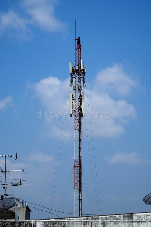 Technician working on cellular telecom pole. High tower with blue sky background stock photos
