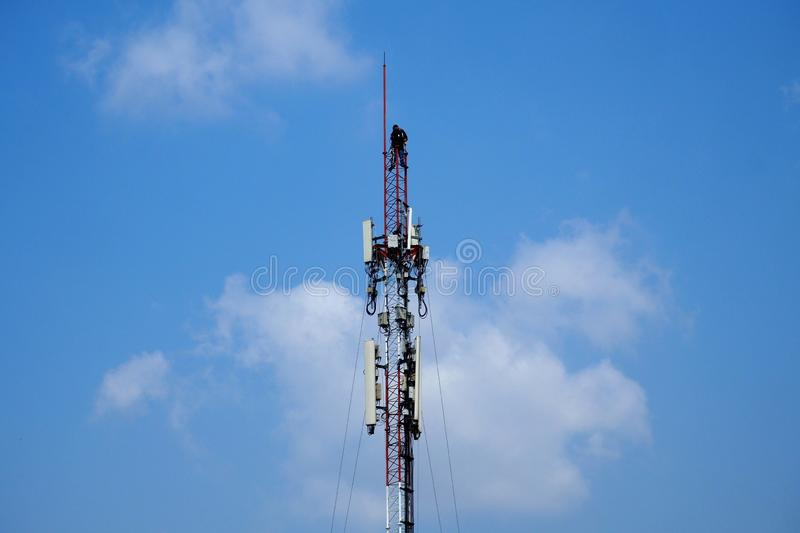Technician working on cellular telecom pole. High tower with blue sky background royalty free stock image