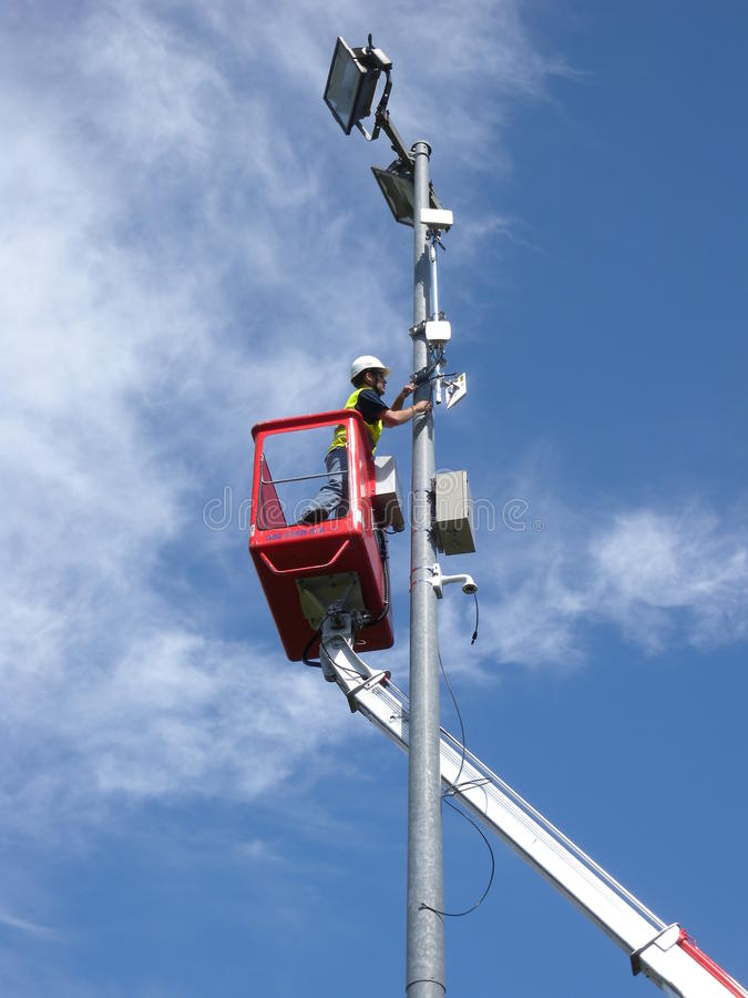 Technician working on pole. Technician working high on a pole using a lift,installing video camera and relays royalty free stock photography