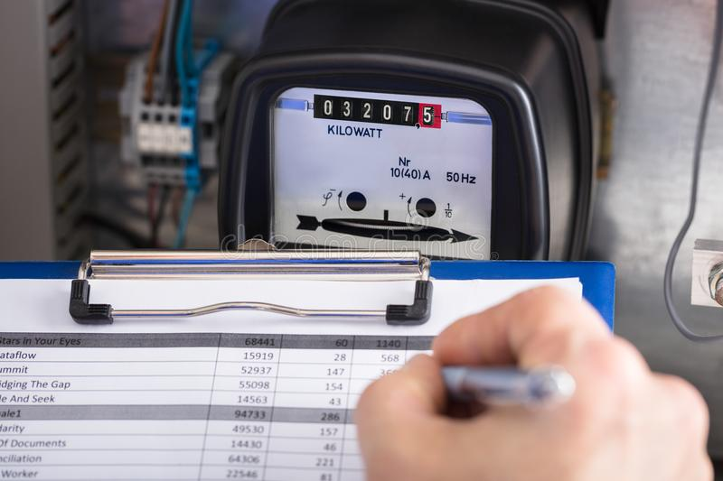 Technician Writing Reading Of Meter On Clipboard royalty free stock image
