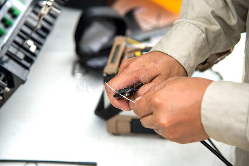 Technicians cutting fiber optic cables. royalty free stock image