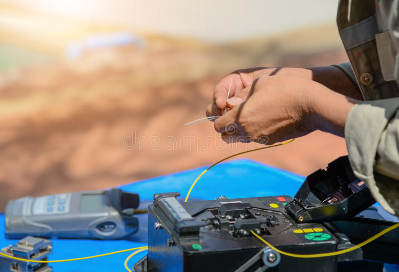 Technicians cutting and fusion fiber optic cables. stock photo