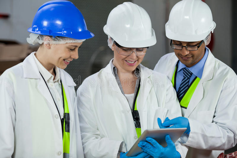 Technicians discussing over digital tablet. At meat factory royalty free stock photography