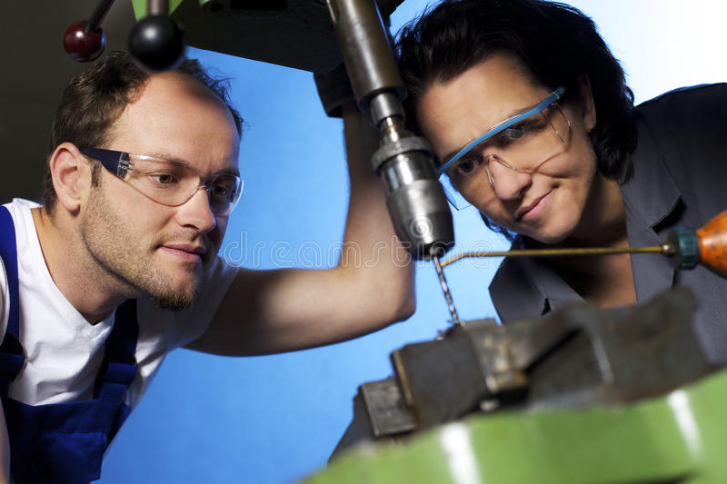 Technicians drilling in workshop. Close-up of young technicians in blue and grey overall working on pillar drilling machine in workshop, blue background, focus stock photos