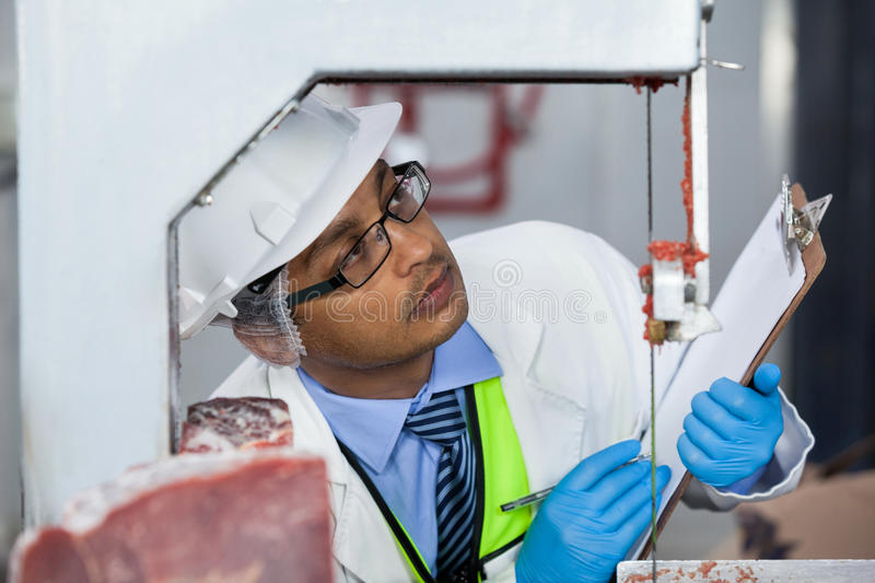 Technicians examining meat band saw. Technicians examining band saw machine at meat factory stock image