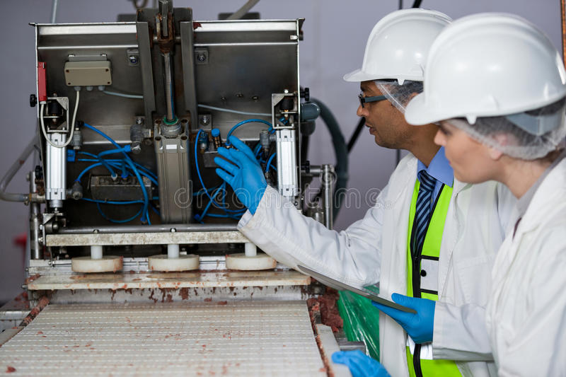 Technicians examining meat processing machine. At meat factory royalty free stock photography