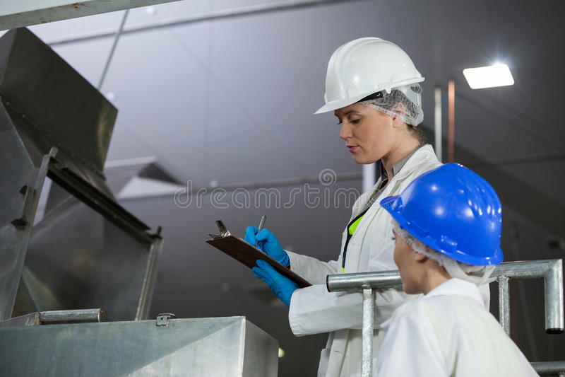 Technicians examining meat processing machine. At meat factory royalty free stock images