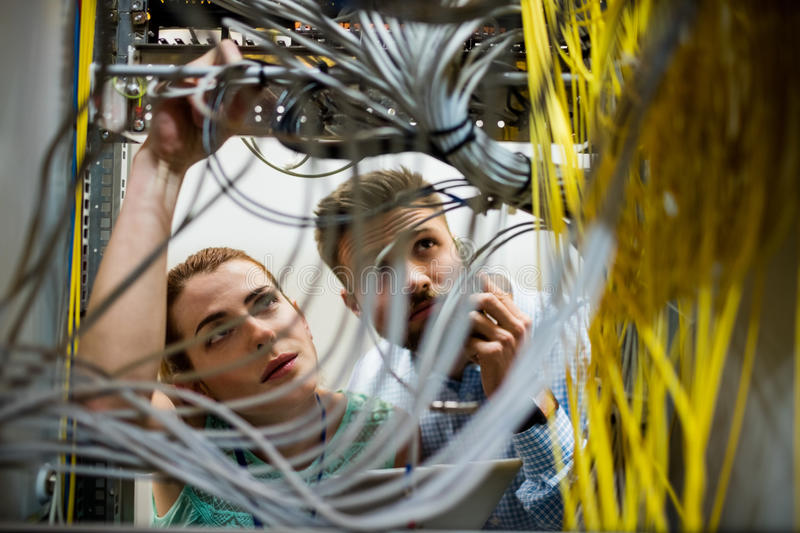 Technicians fixing cable. In server room royalty free stock photos