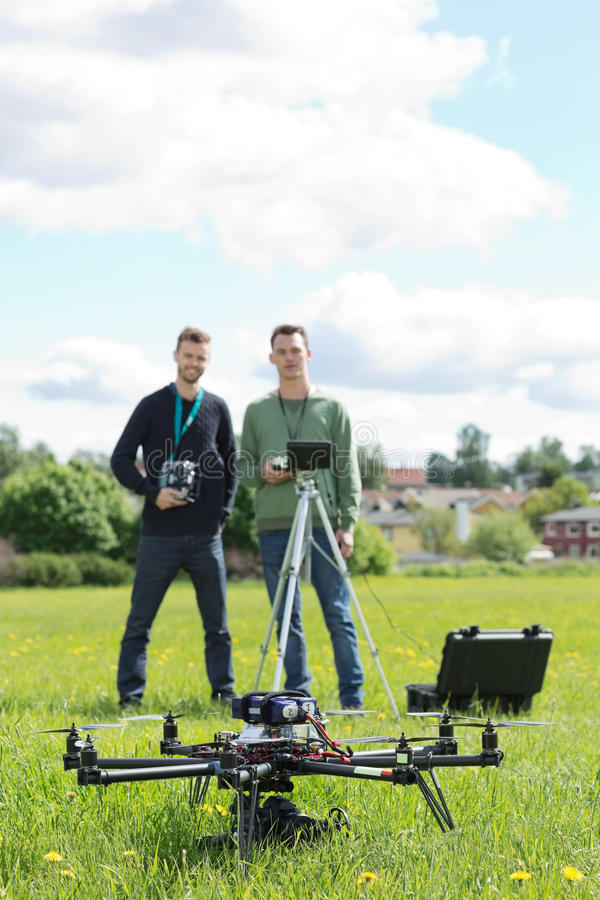 Technicians Holding Remote Controls Of UAV. Young technicians holding remote controls with UAV helicopter in foreground at park stock photos