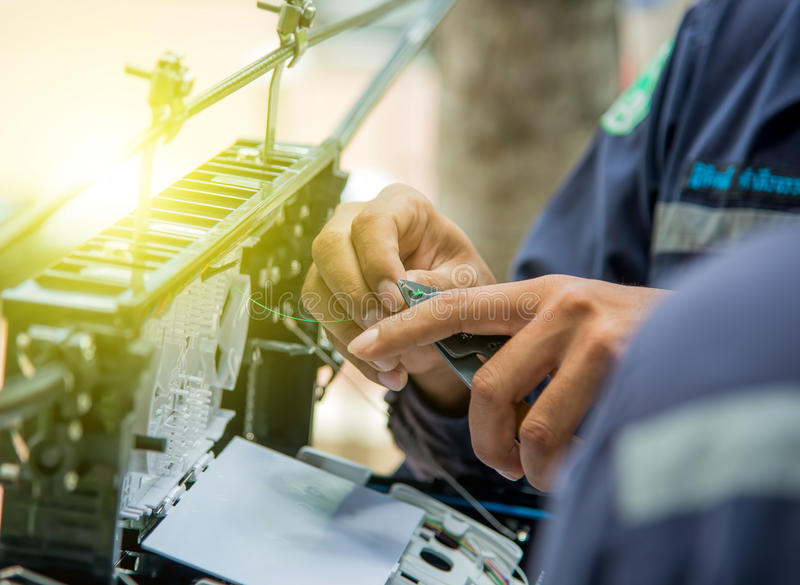 Technicians install cabinet on fiber optic cable. Technicians are install cabinet on fiber optic cable.Blur images with back lighting stock photo