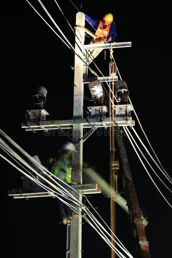 Technicians Working on Electrical Pole at Night. Technicians Installing High Voltage Equipment on Electrical Pole at Night Time stock images