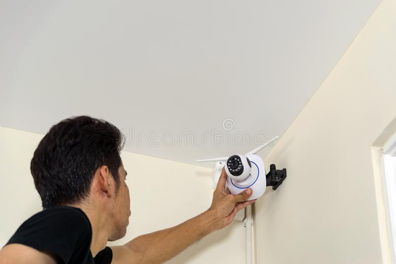 Technicians are installing a wireless cctv camera. On the roof, can connect to the Internet, and control the camera via a smartphone or tablet royalty free stock images