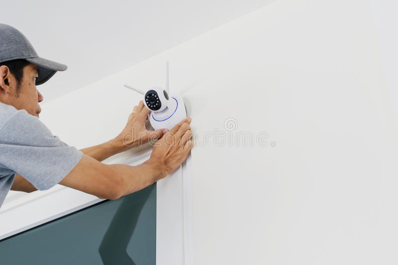 Technicians are installing a wireless cctv camera. On the wall, can connect to the Internet, and control the camera via a smartphone or tablet stock photo