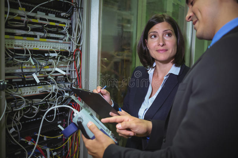 Technicians interacting with each other while analyzing server. In server room royalty free stock photo
