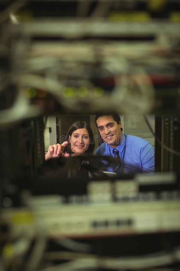 Technicians interacting with each other while analyzing server. In server room stock photo