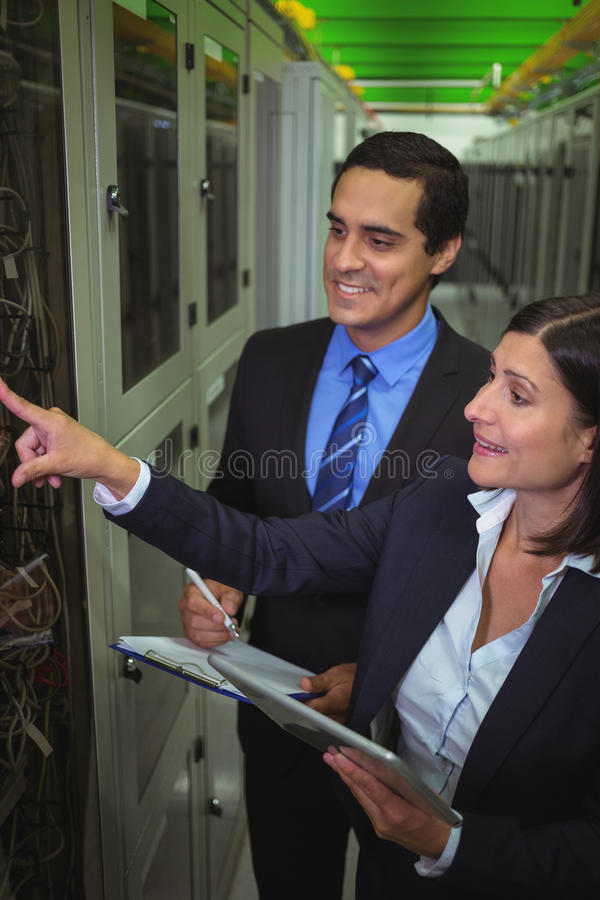 Technicians interacting with each other while analyzing server. In server room stock photography