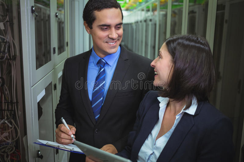 Technicians interacting with each other while analyzing server. In server room royalty free stock photos