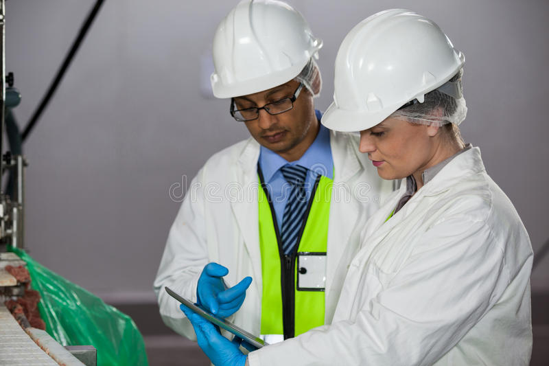 Technicians looking at digital tablet. In meat factory stock image